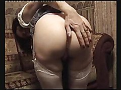 Aged doxy undresses and masturbates on the couch